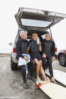 A group of senior surfers in their wet suits sitting on the tailgate of a pickup. Two men with gray hair and one older woman taking a break from surfing. Surfing is the favorite sport for these mature retired men and women.